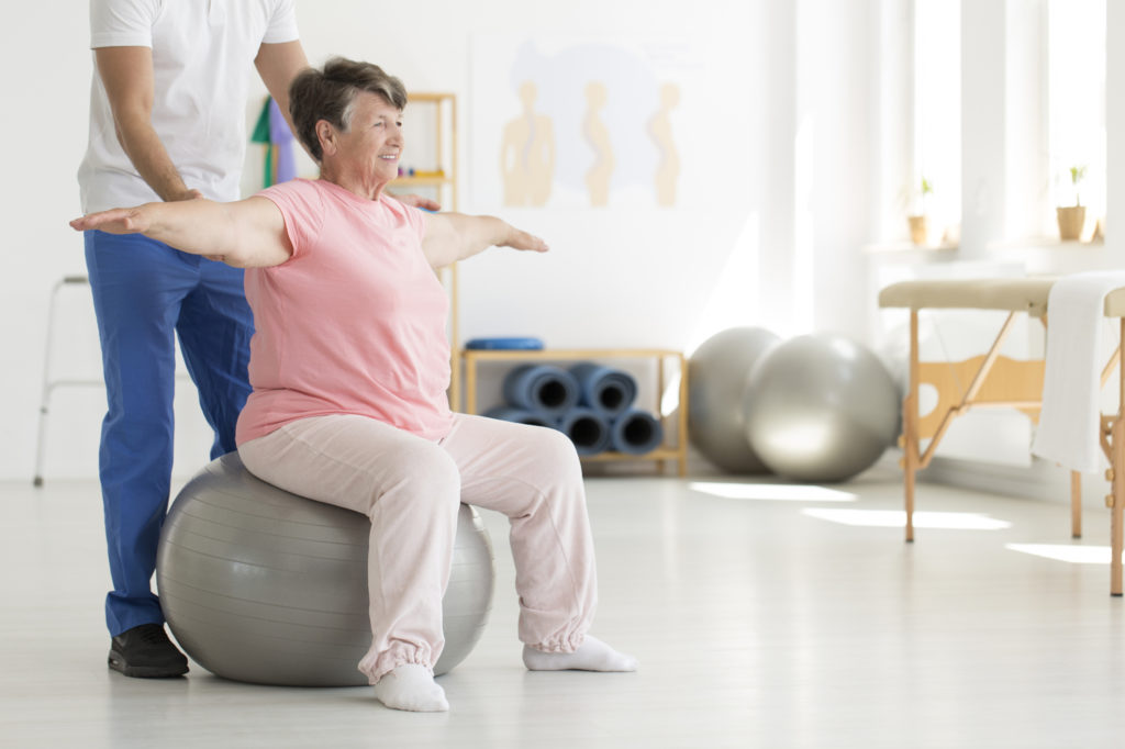 older woman balancing on ball with help from physical therapist