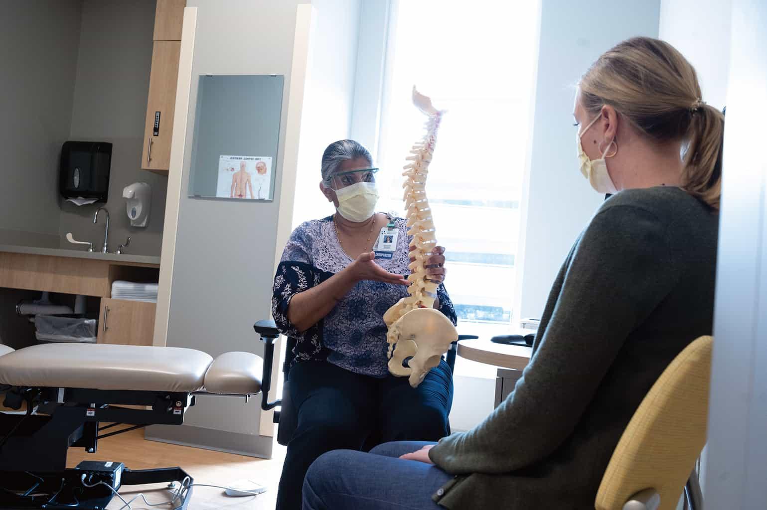 chiropractor showing spine model patient