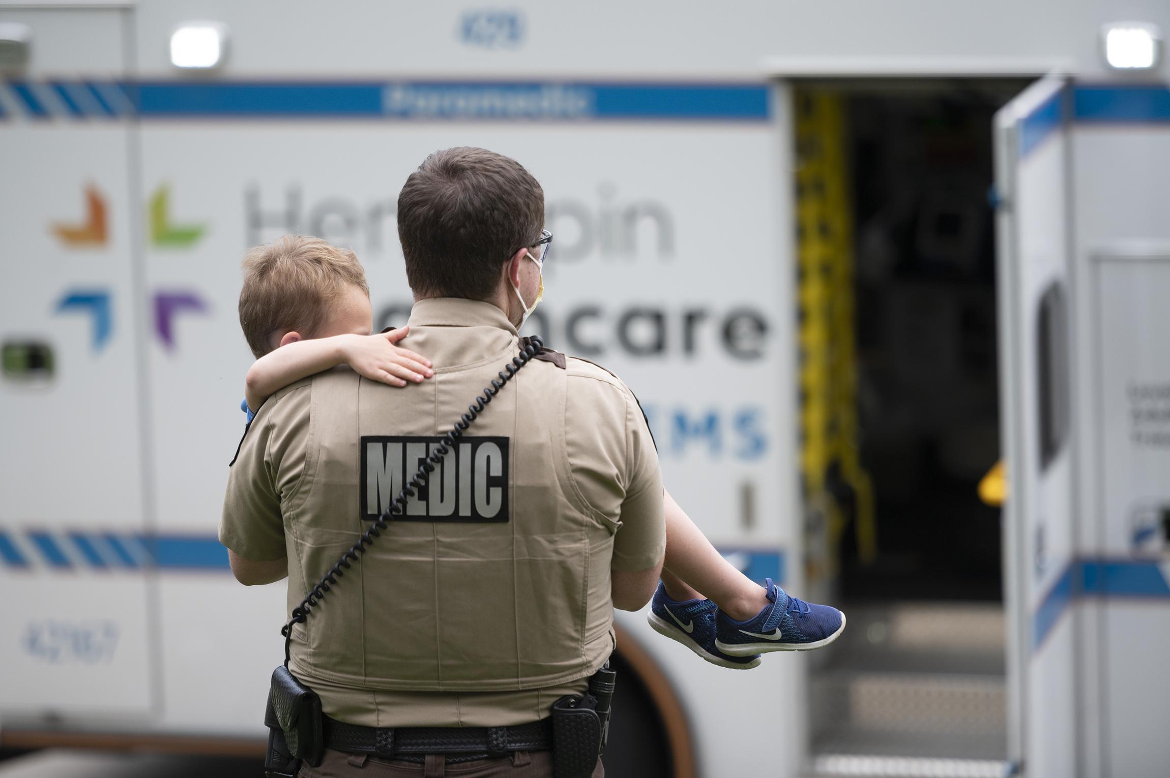 paramedic carrying child to ambulance