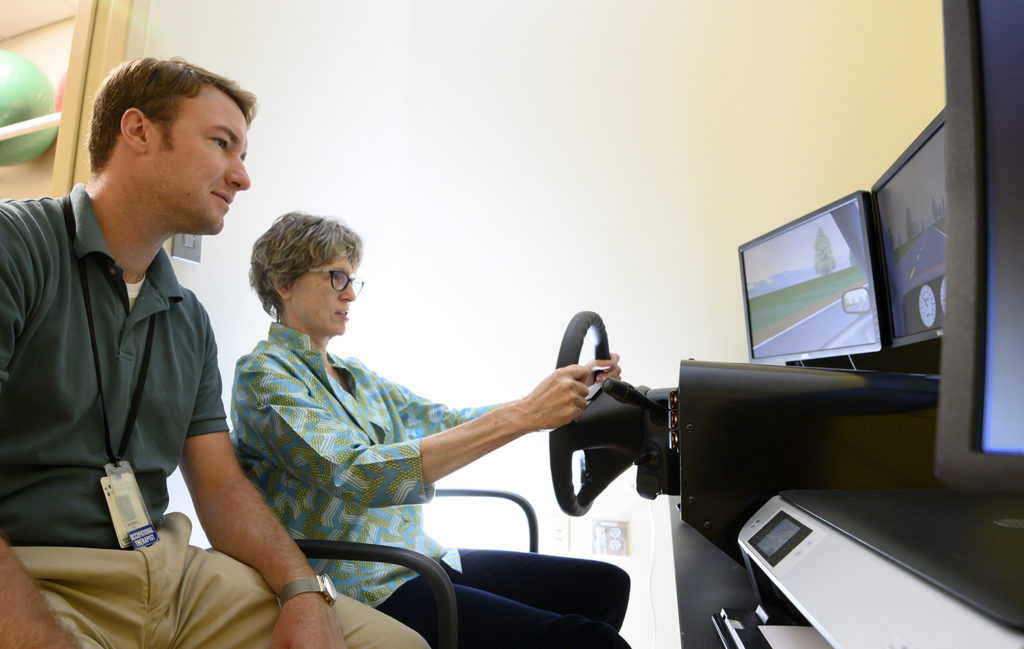 tbi therapist with patient and drive simulator