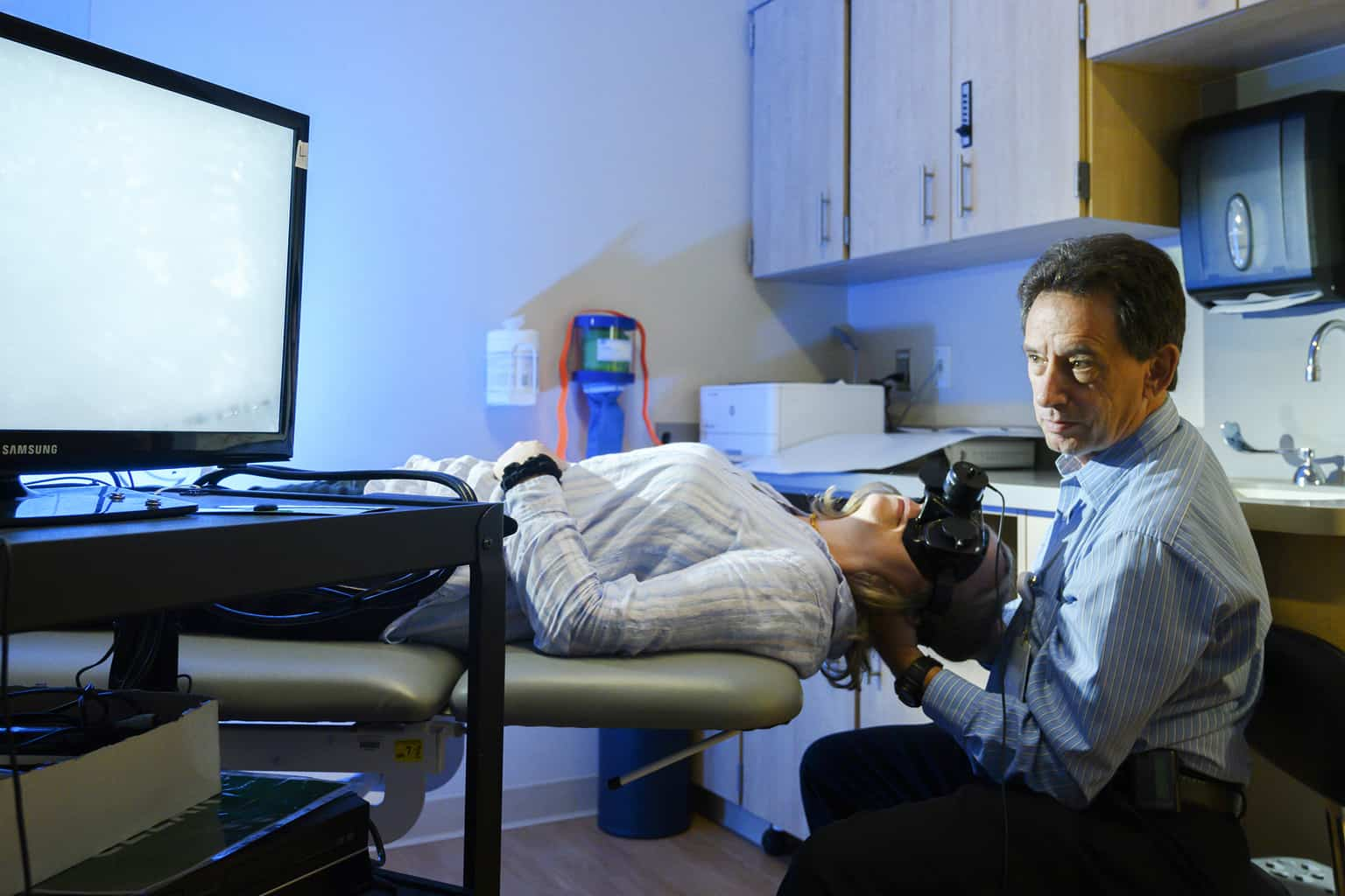 physical therapist with reclining patient in vestibular rehabilitation clinic room