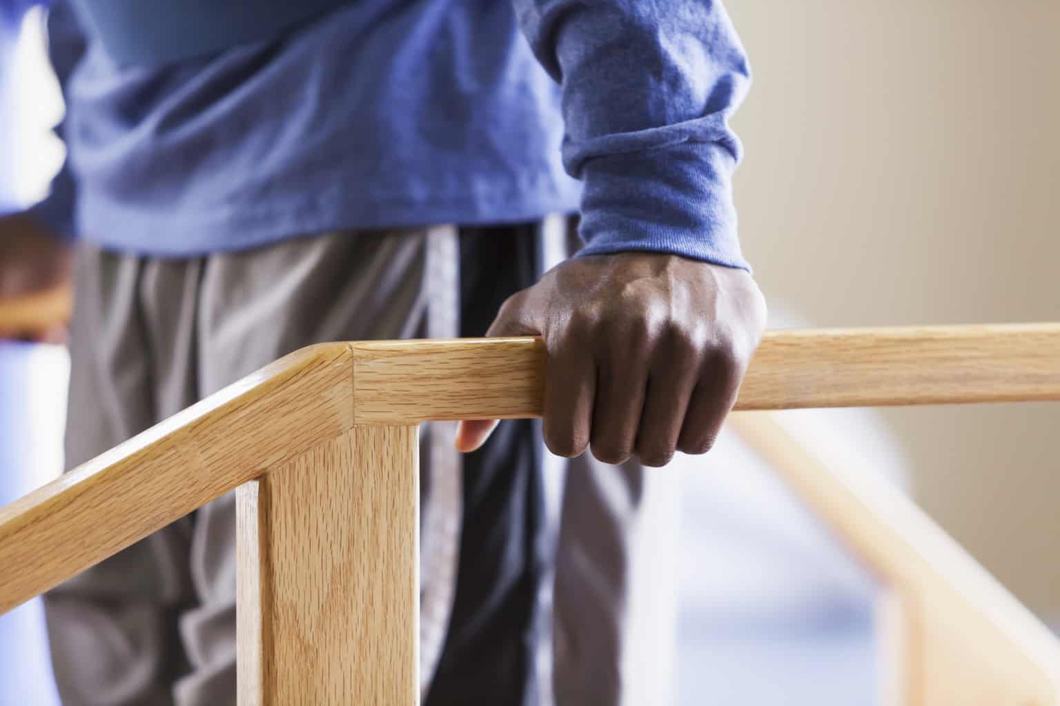 Close up of an African American man using a physical therapy exercise staircase.  It is a cropped view of his midsection, with his hand grasping the railing of the staircase.