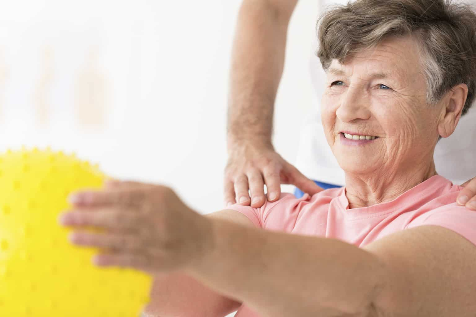A close-up portrait of an elderly woman holding a ball in physiotherapy with doctor's hands on her shoulders