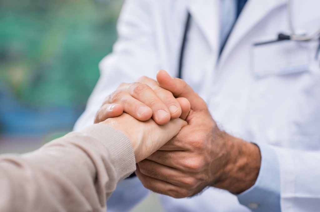 provider holding patient hand