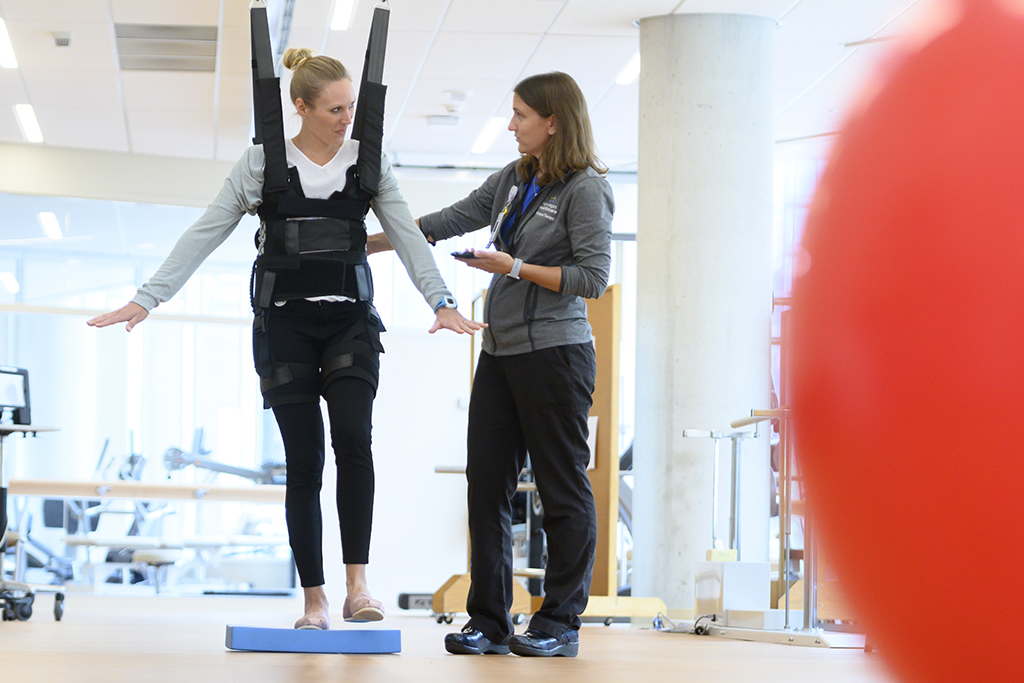 physical therapy patient using suspension device with tech