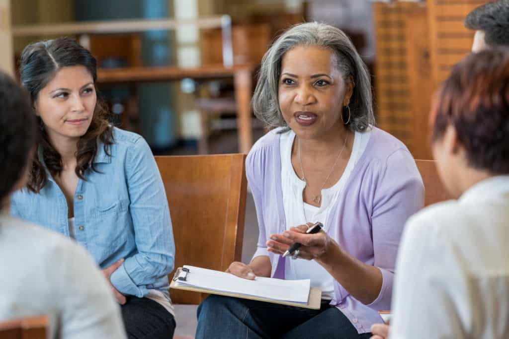 Serious senior African American female mental health profession gestures while talking with clients in a support group or group therapy session. She is holding a clipboard.