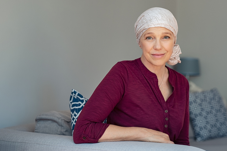 Mature woman with cancer in pink headscarf smiling sitting on couch at home. Smiling woman suffering from cancer sitting after taking chemotherapy sessions. Portrait of mature lady facing side-effects of hair loss, copy space.