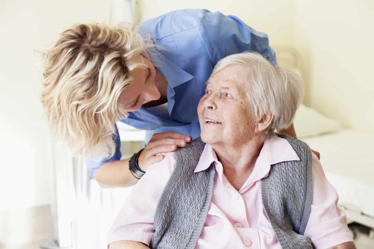 elderly woman in chair with tech home care