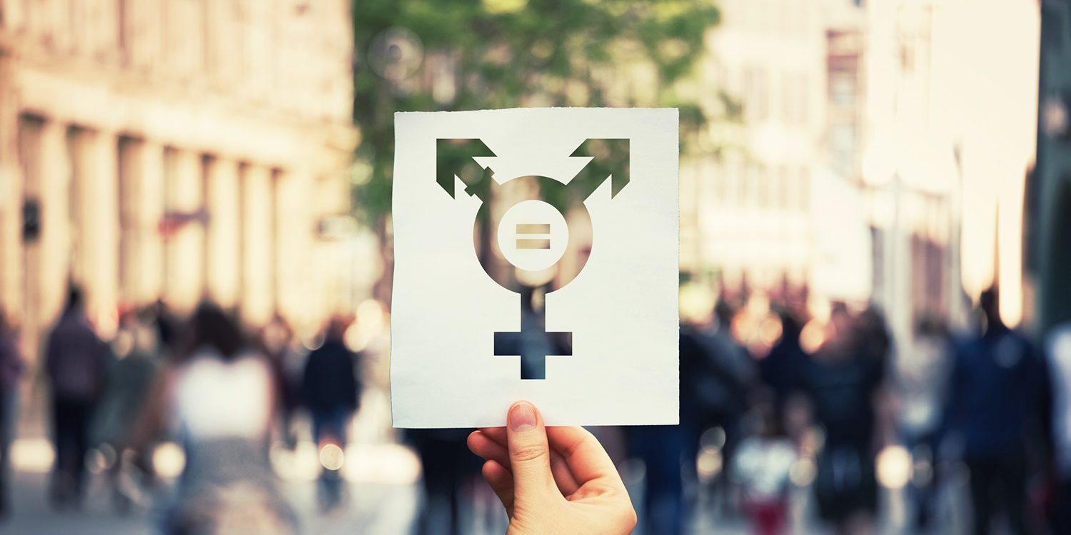 Hand holding a paper sheet with transgender symbol and equal sign inside. Equality between genders concept over a crowded city street background. Sex rights as a metaphor of social issue.
