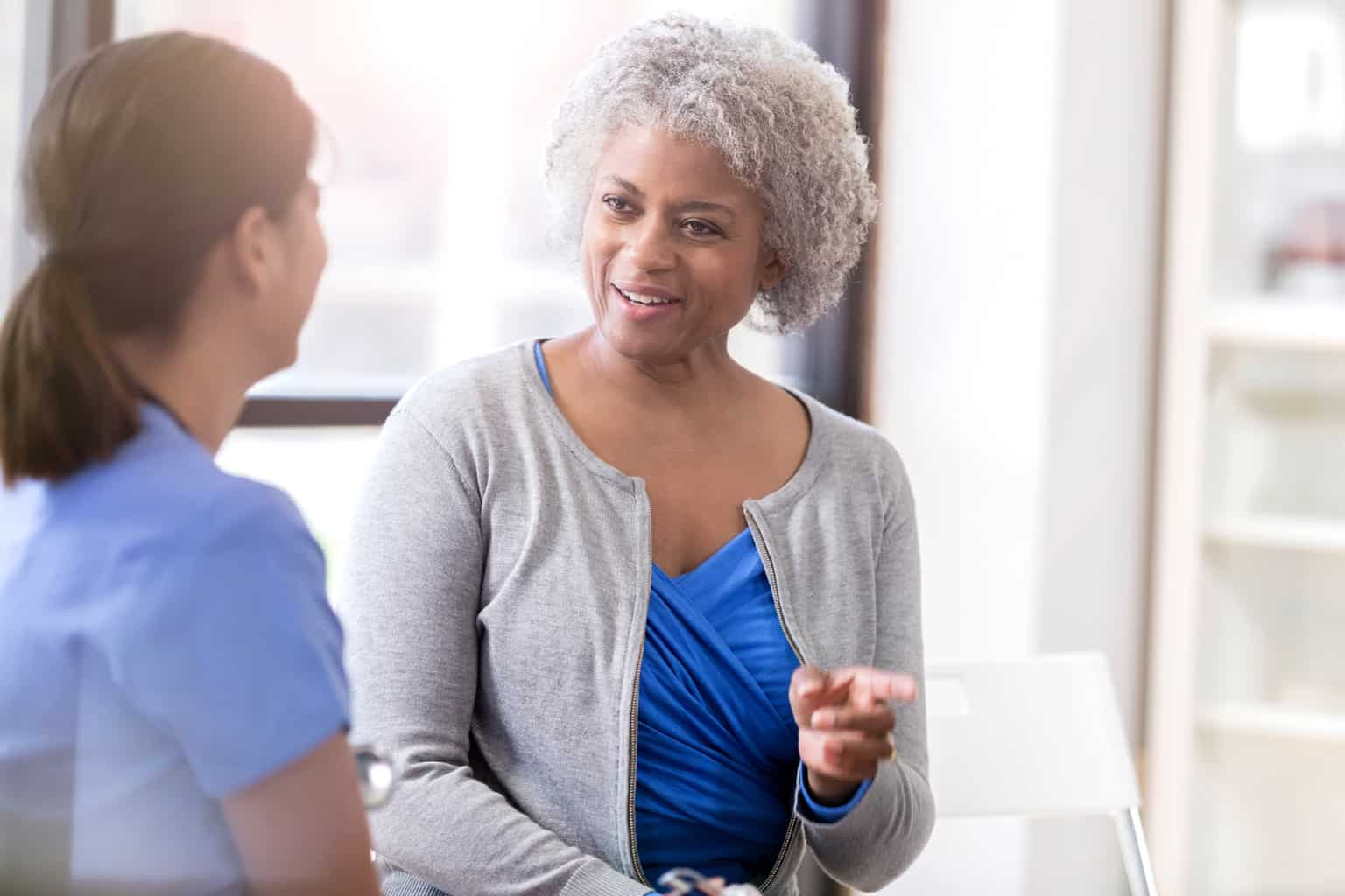 african american woman patient with doctor in clinic