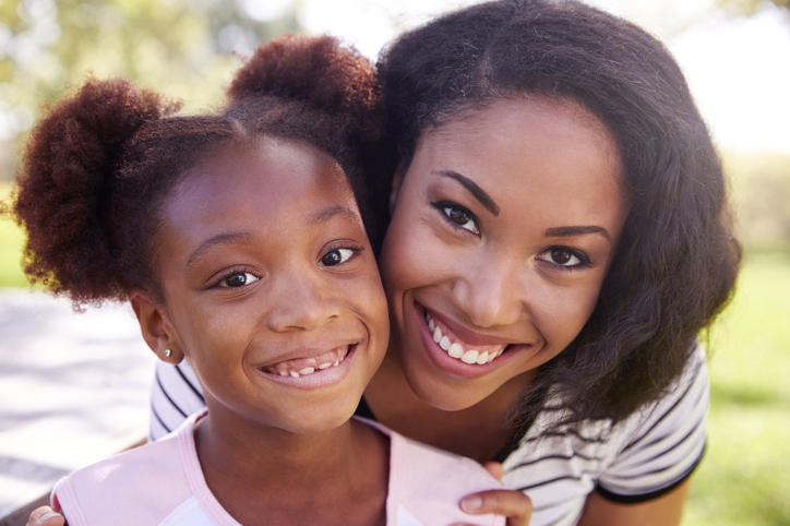 mom with daughter smiling outside