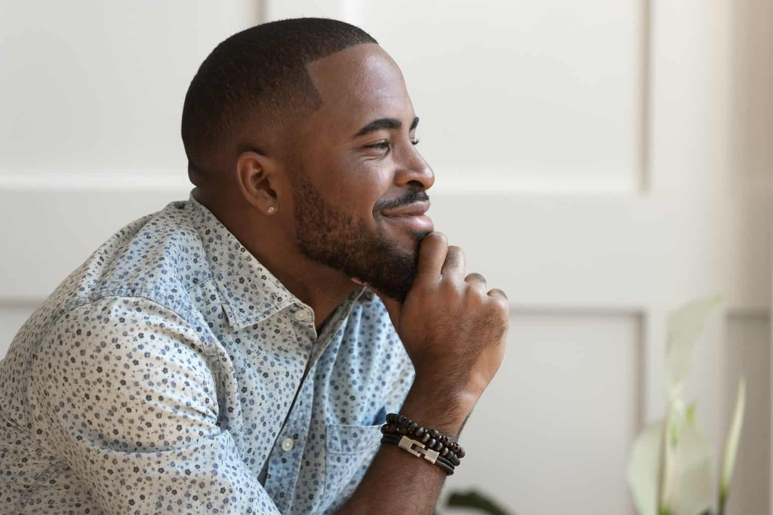 Dreamy calm african american young man looking away contemplating daydreaming sitting at home, thoughtful happy black guy dreaming thinking of good future, hoping meditating enjoy peace of mind