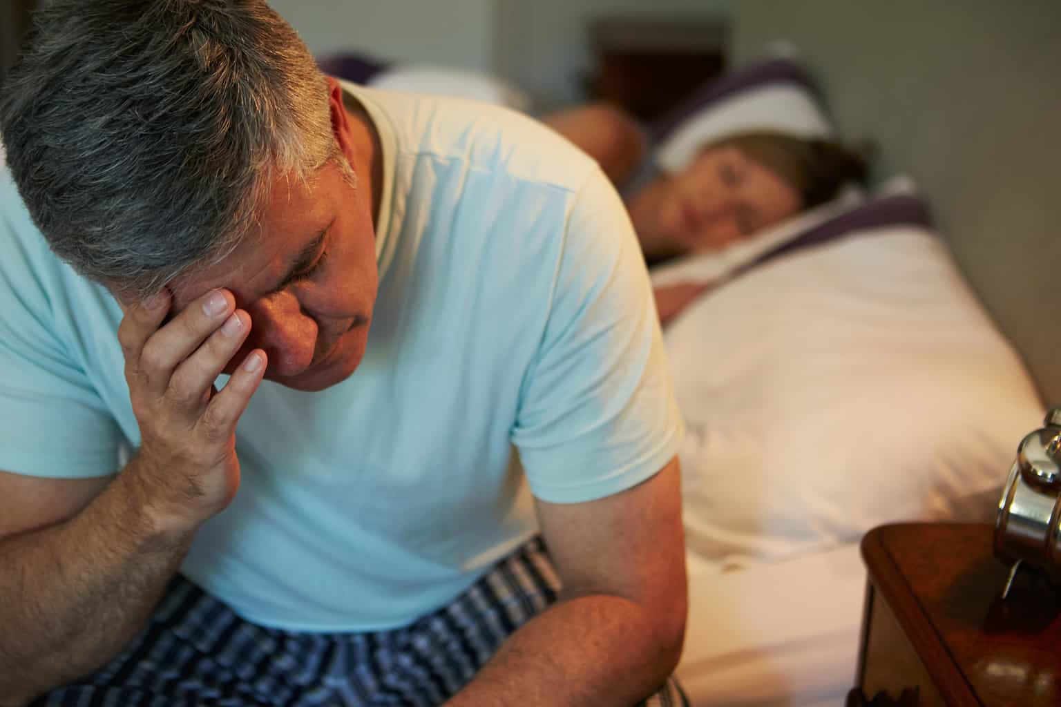 man with insomnia sitting on bed